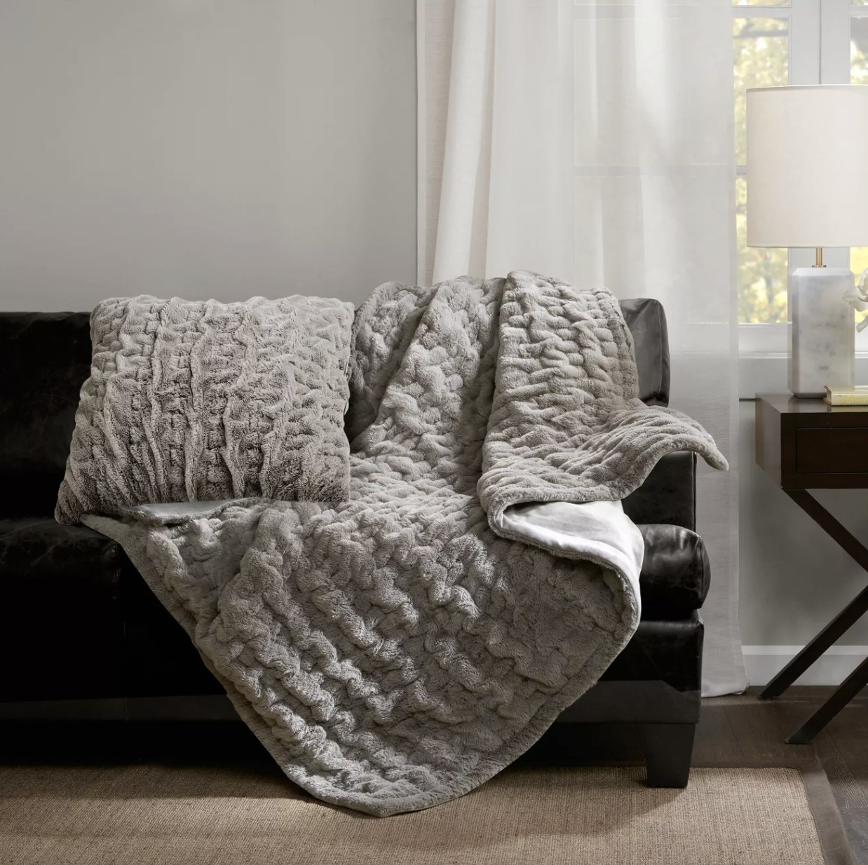 a ruched faux fur throw blanket in grey draped over a couch in a living room