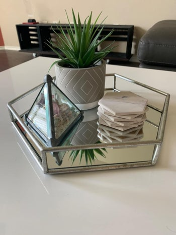 a reviewer's hexagon-shaped silver tray with a mirrored base filled with coasters, a terrarium, and a plant