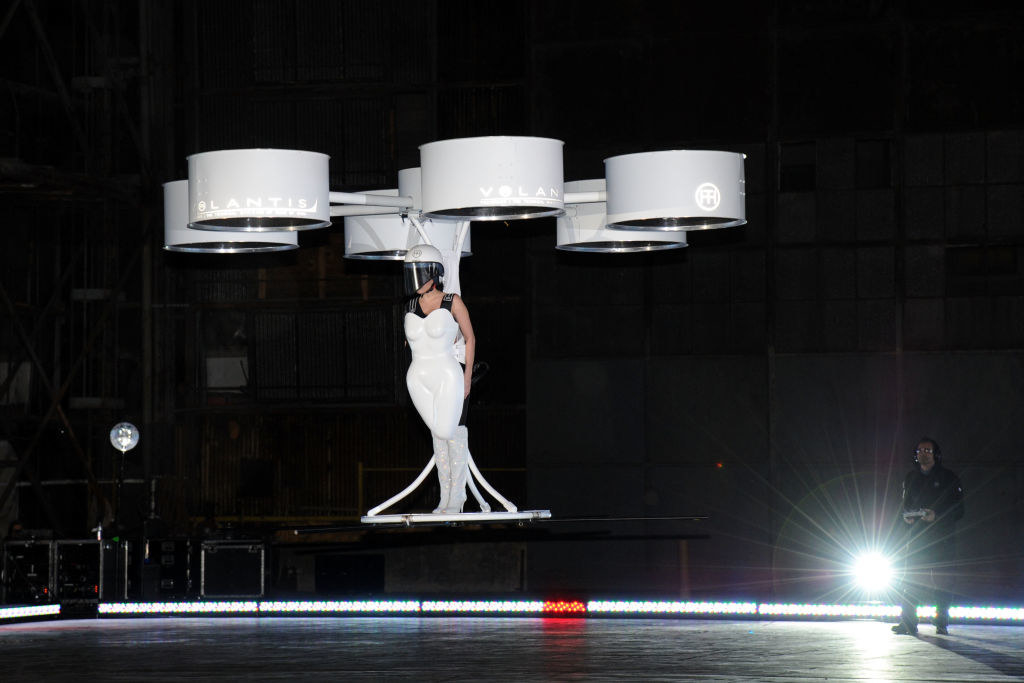 Lady Gaga being carried by six propellers that are attatched to a white dress shaped like a body