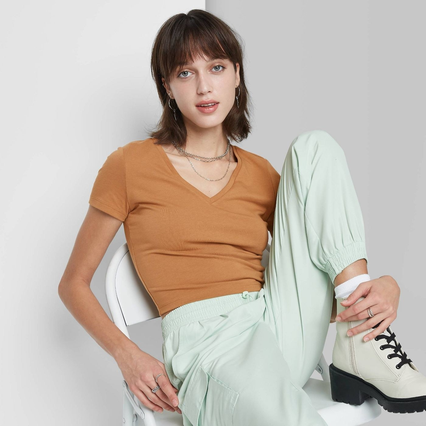 Model wearing mustard yellow shirt, stops at the waist