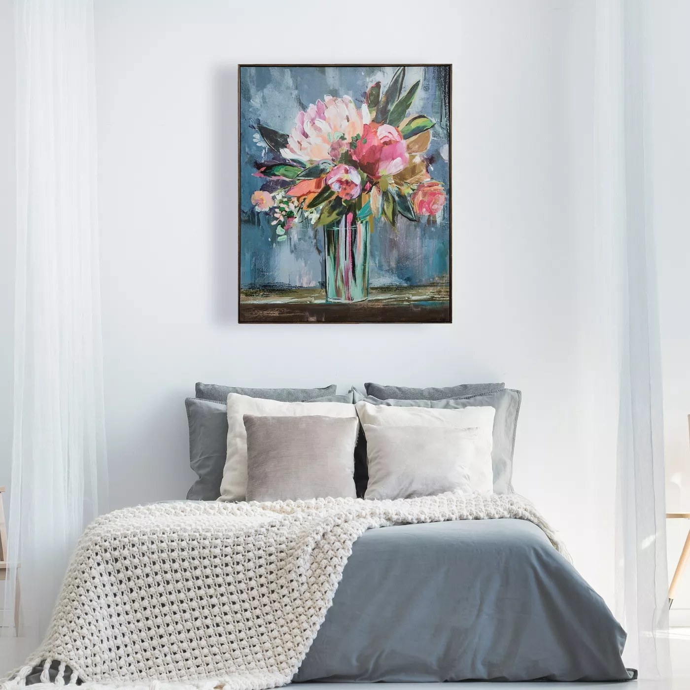 The painting of a vase filled with pink flowers on a blue background hanging in a bedroom