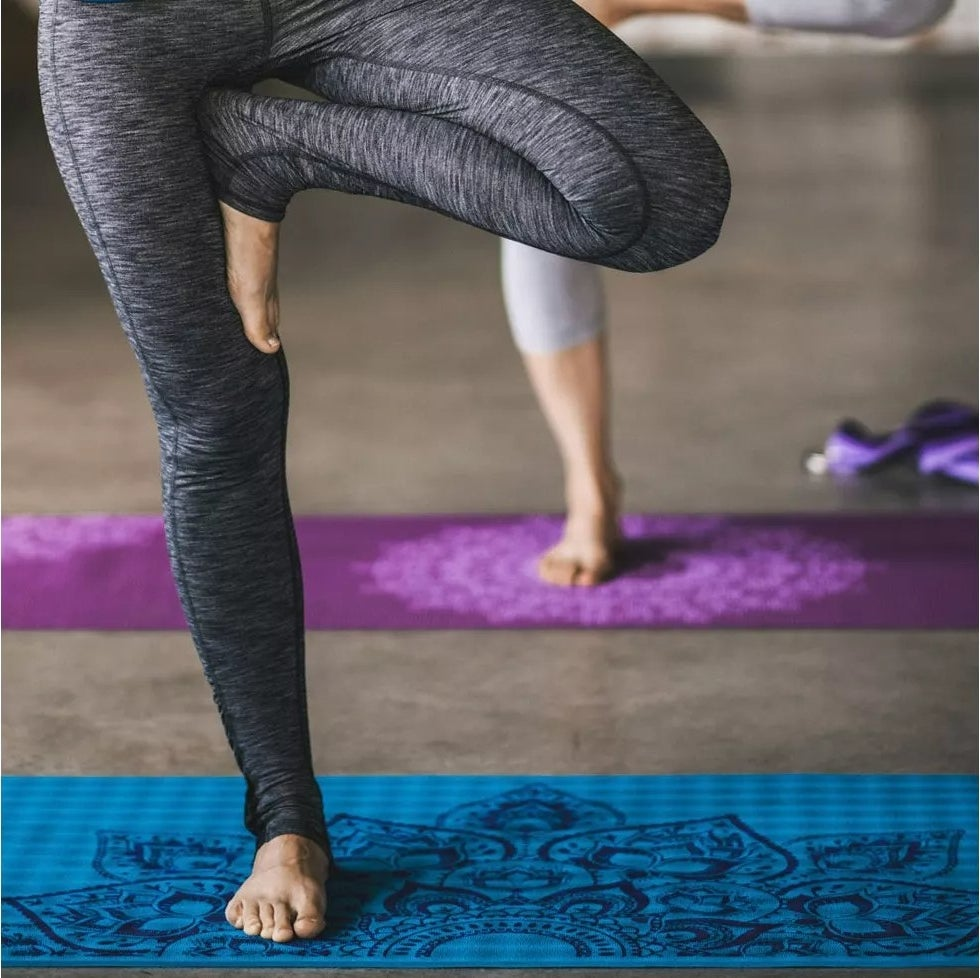 A model practicing yoga on the printed yoga mat