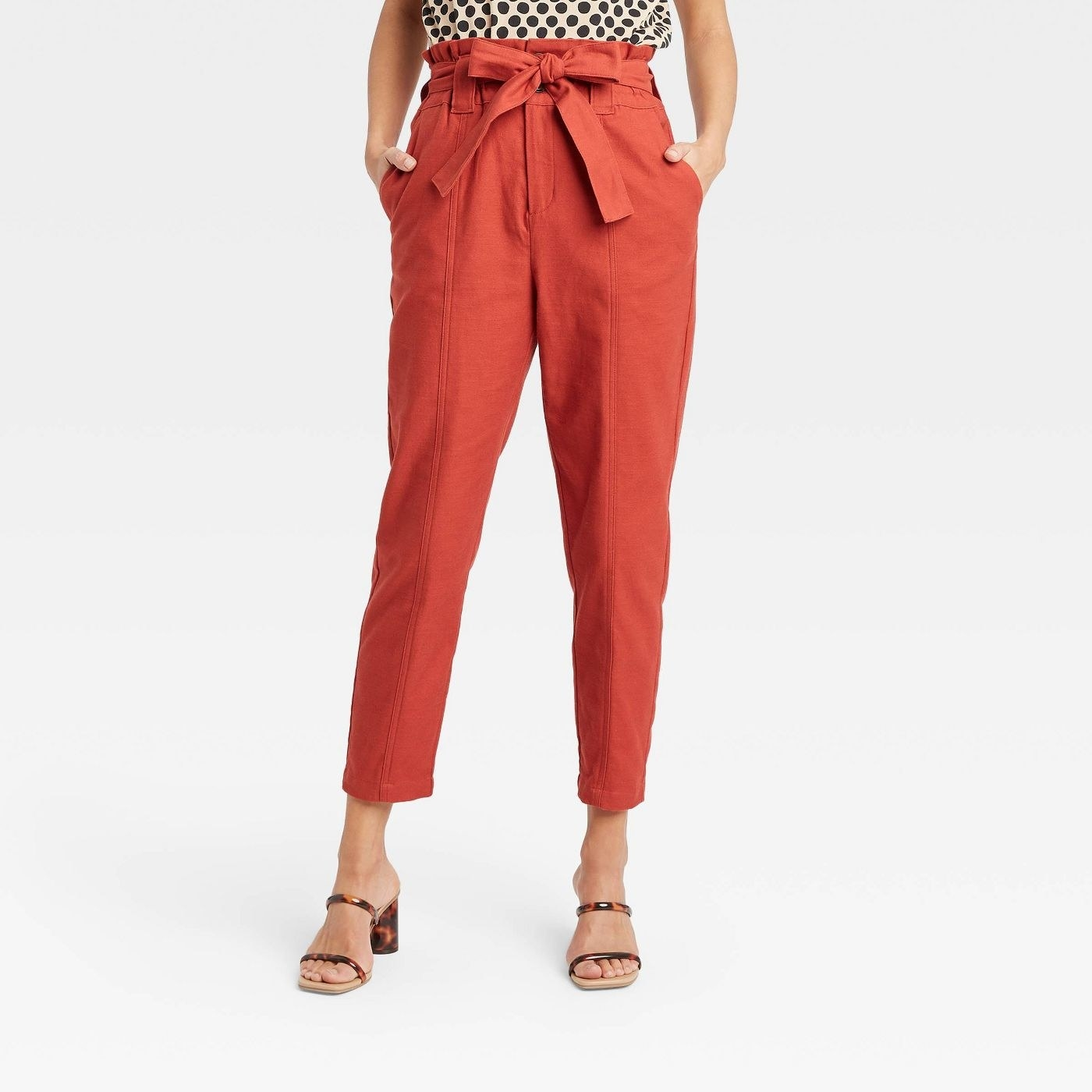 Model wearing orange high waisted pants with a tie waist, stops at the ankle