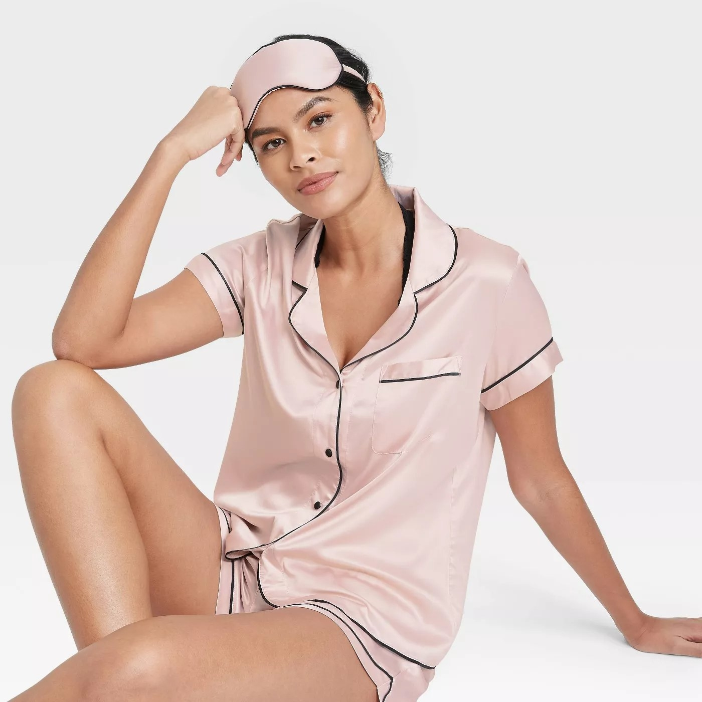 A model wearing the pale pink pajama set with black piping.