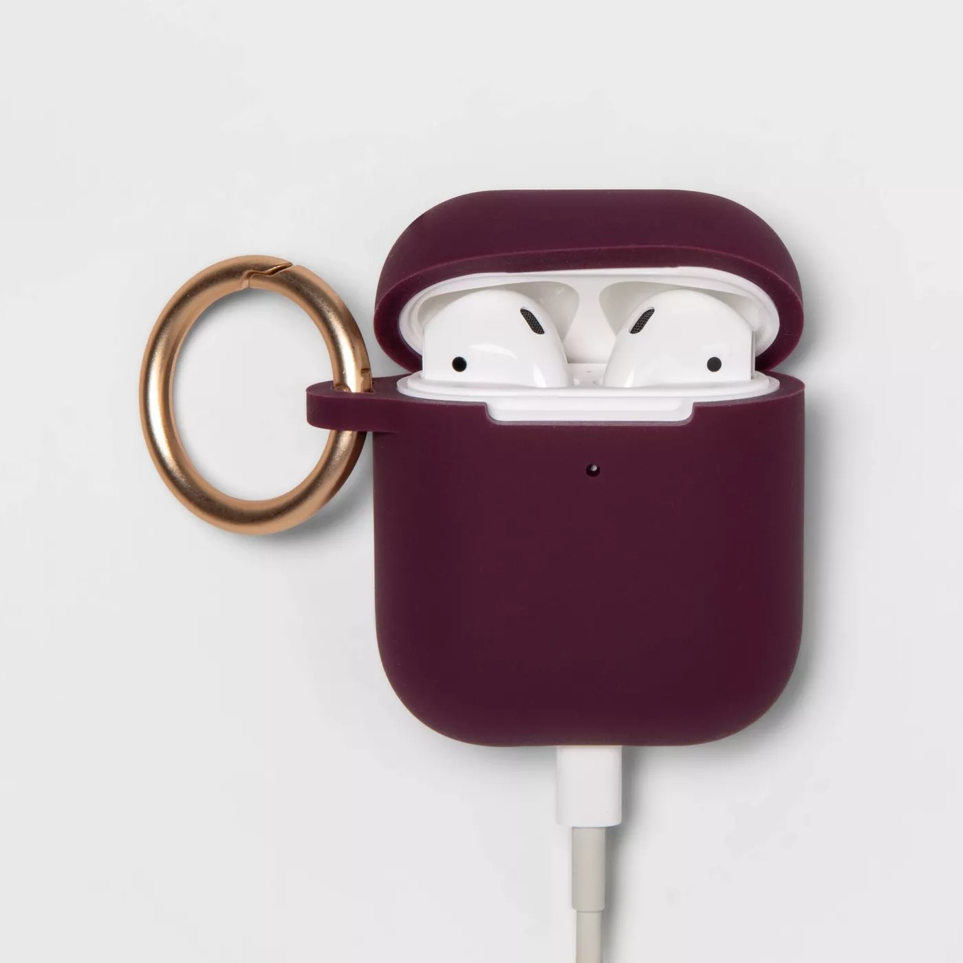 The Airpod case with Airpods inside and a gold carabiner clip
