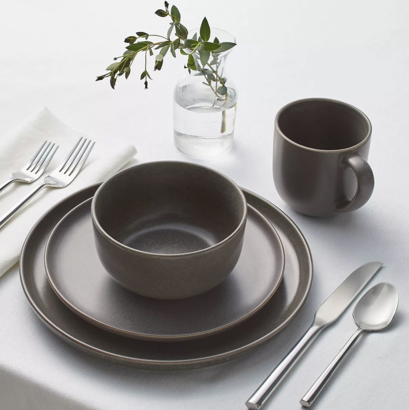 a brown stoneware mug, bowl, appetizer plate and dinner plate at a place setting