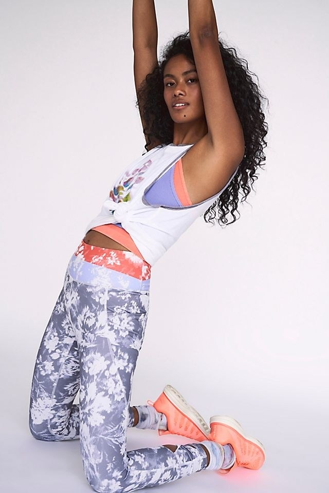 Model wearing the blue-gray leggings with a light blue and coral colorblocked waistband and white abstract floral print
