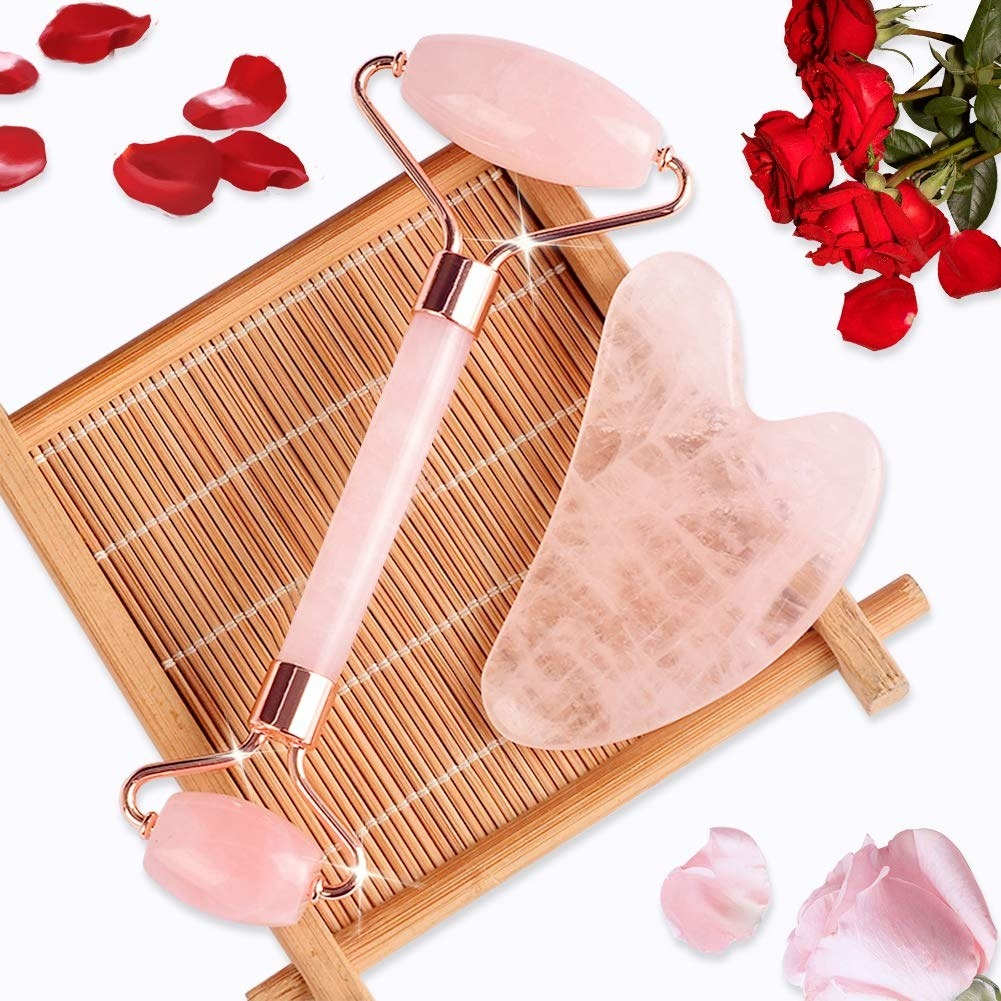 Rose quartz roller and gua shua tool lying on bamboo tray
