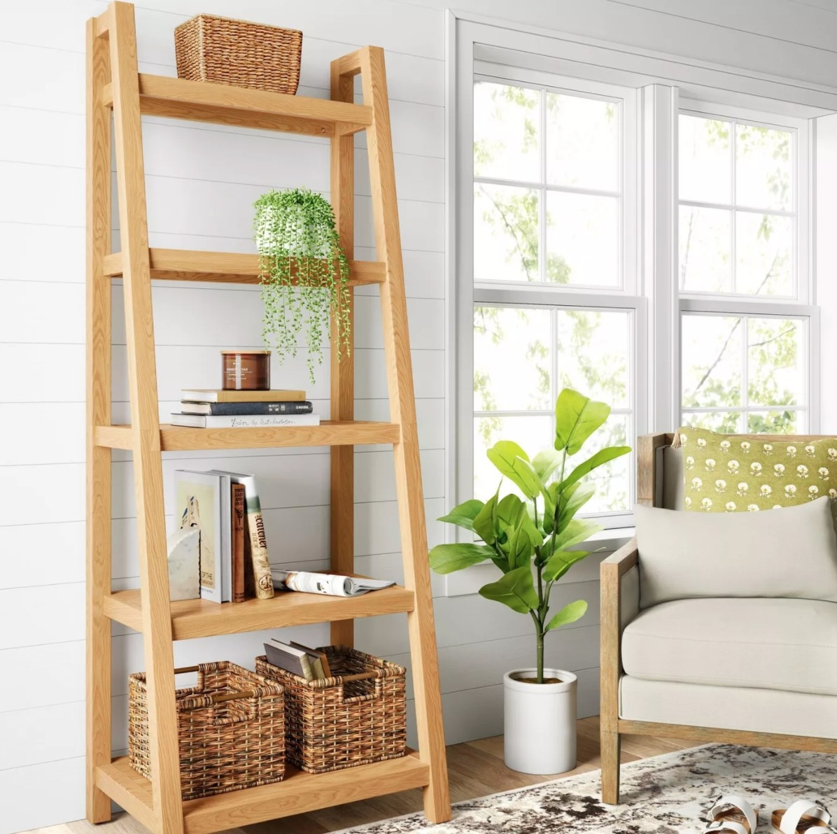 The wood ladder bookcase holding books, plants, and baskets