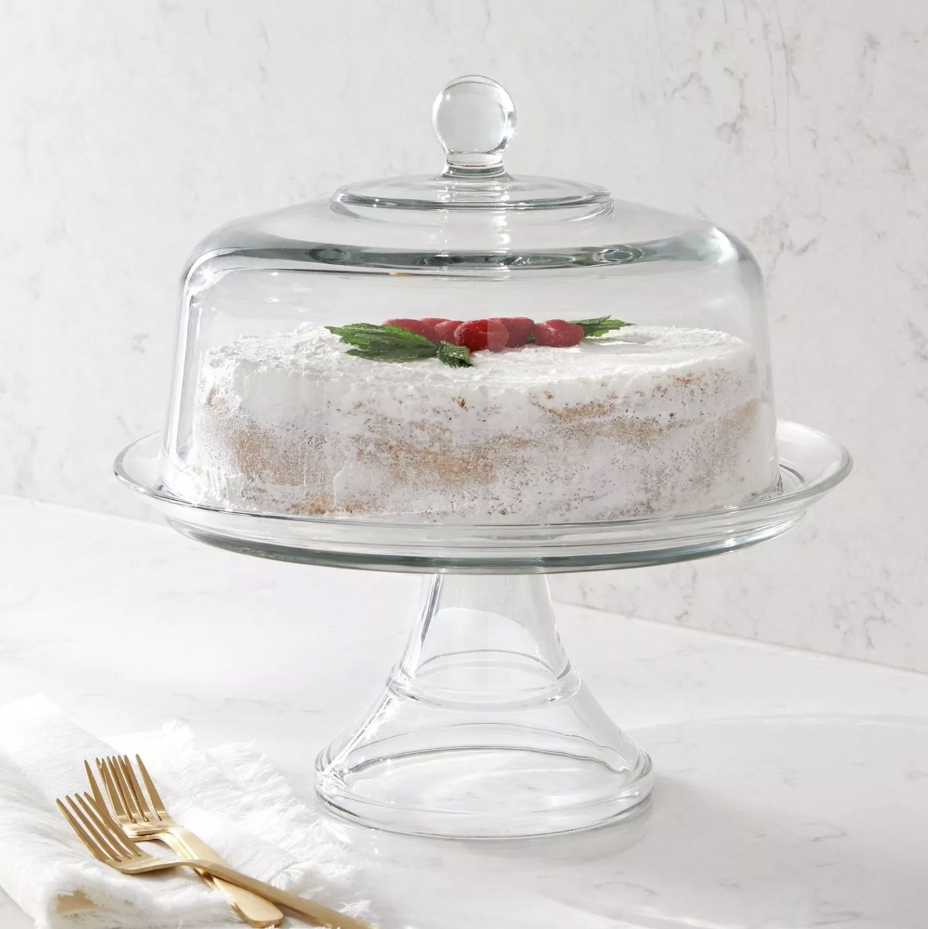 a glass cake stand with a lid holding a cake on a kitchen counter