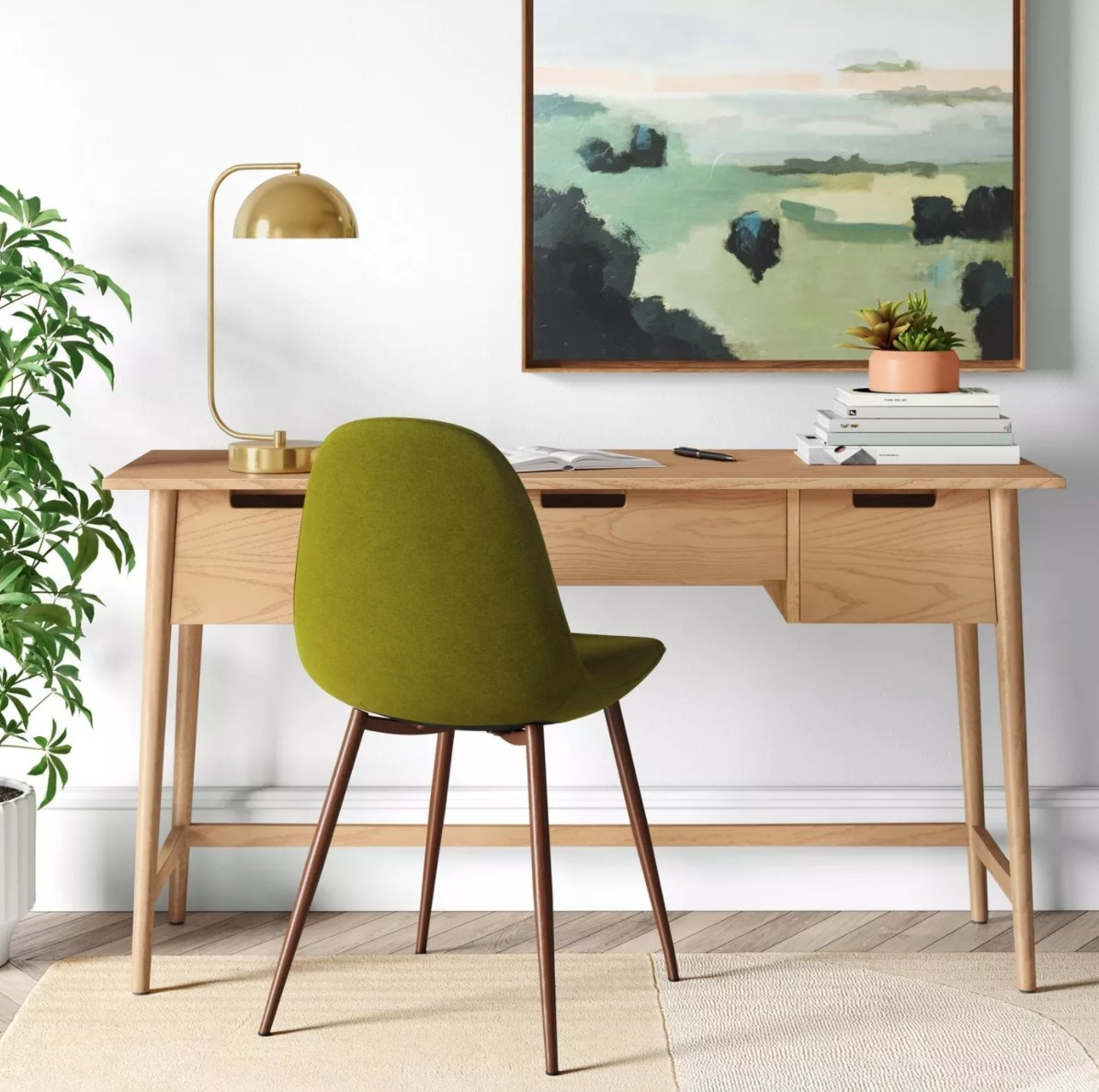 The large wood writing desk in natural with a green felt chair in front of it