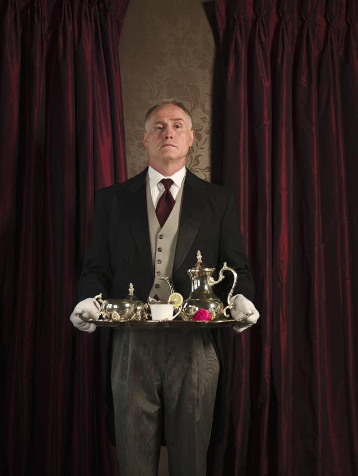 a butler holding a fancy serving tray