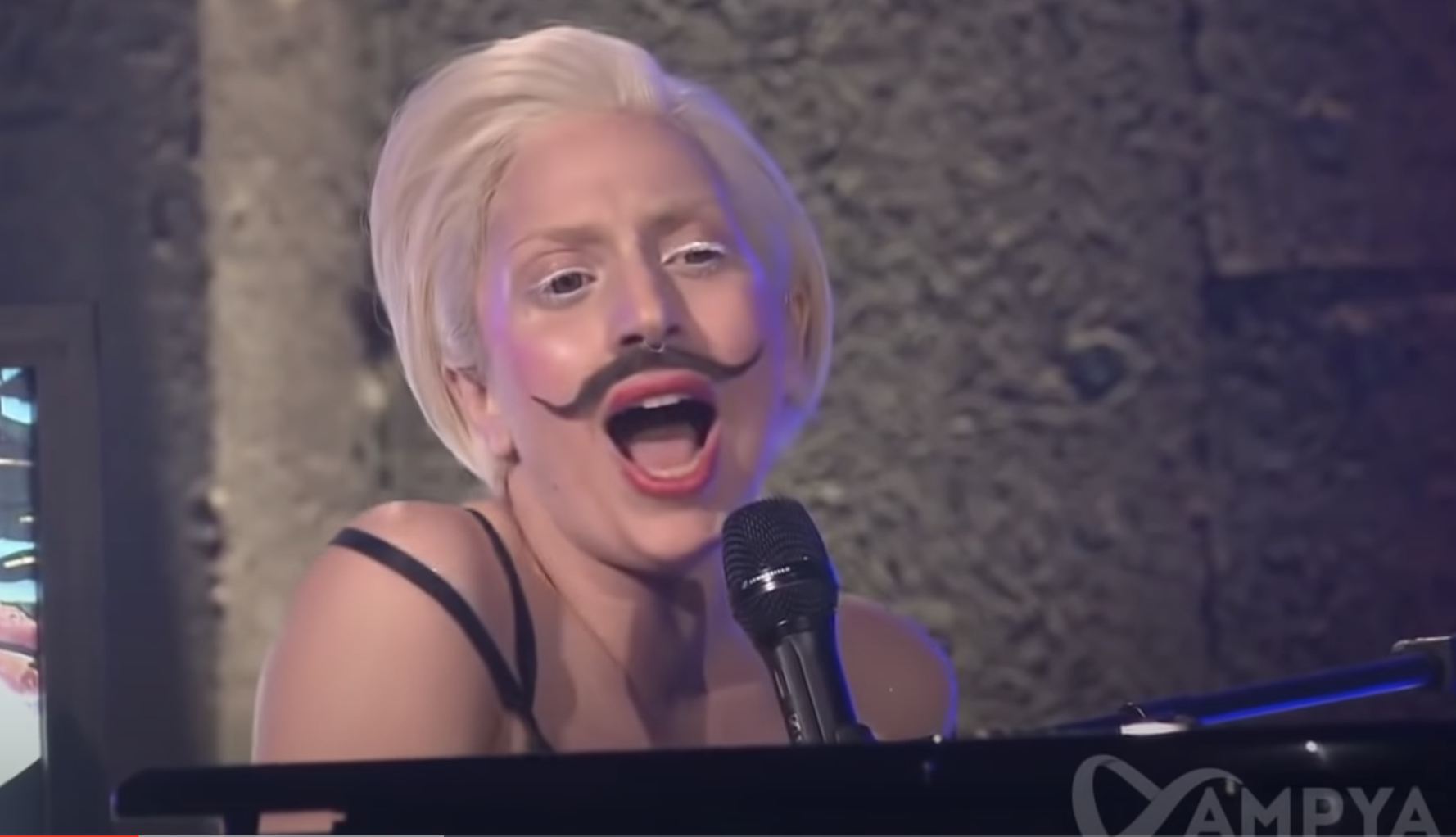 Gaga in white eyeliner and a fake handlebar mustache while at the piano singing Gypsy