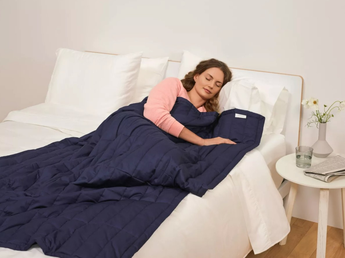 The Casper weighted blanket in navy blue being used by a model