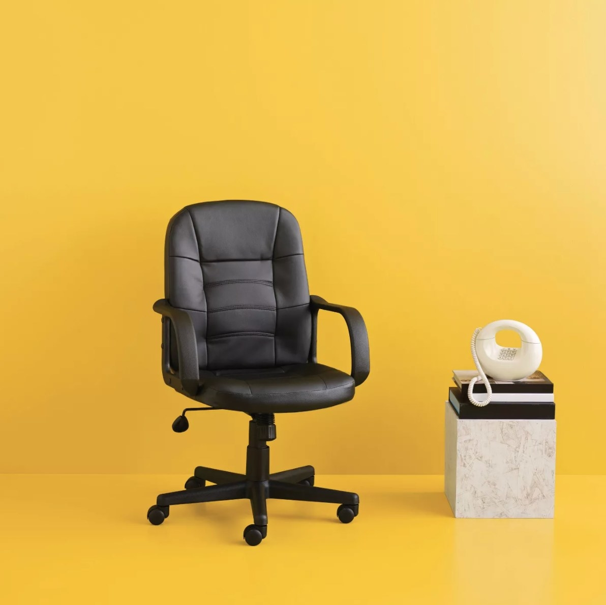 The leather office chair on a yellow backdrop