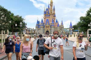 Guests wearing face masks stroll on Main Street in front of Cinderella's Castle in Disney World