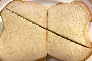 Two sandwiches cut diagonally where the halves are wildly different sizes