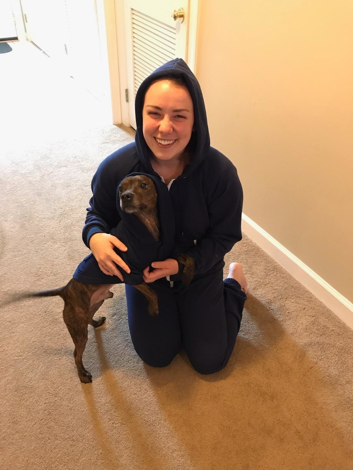 A dog and human wear the matching jogger onesies in dark blue