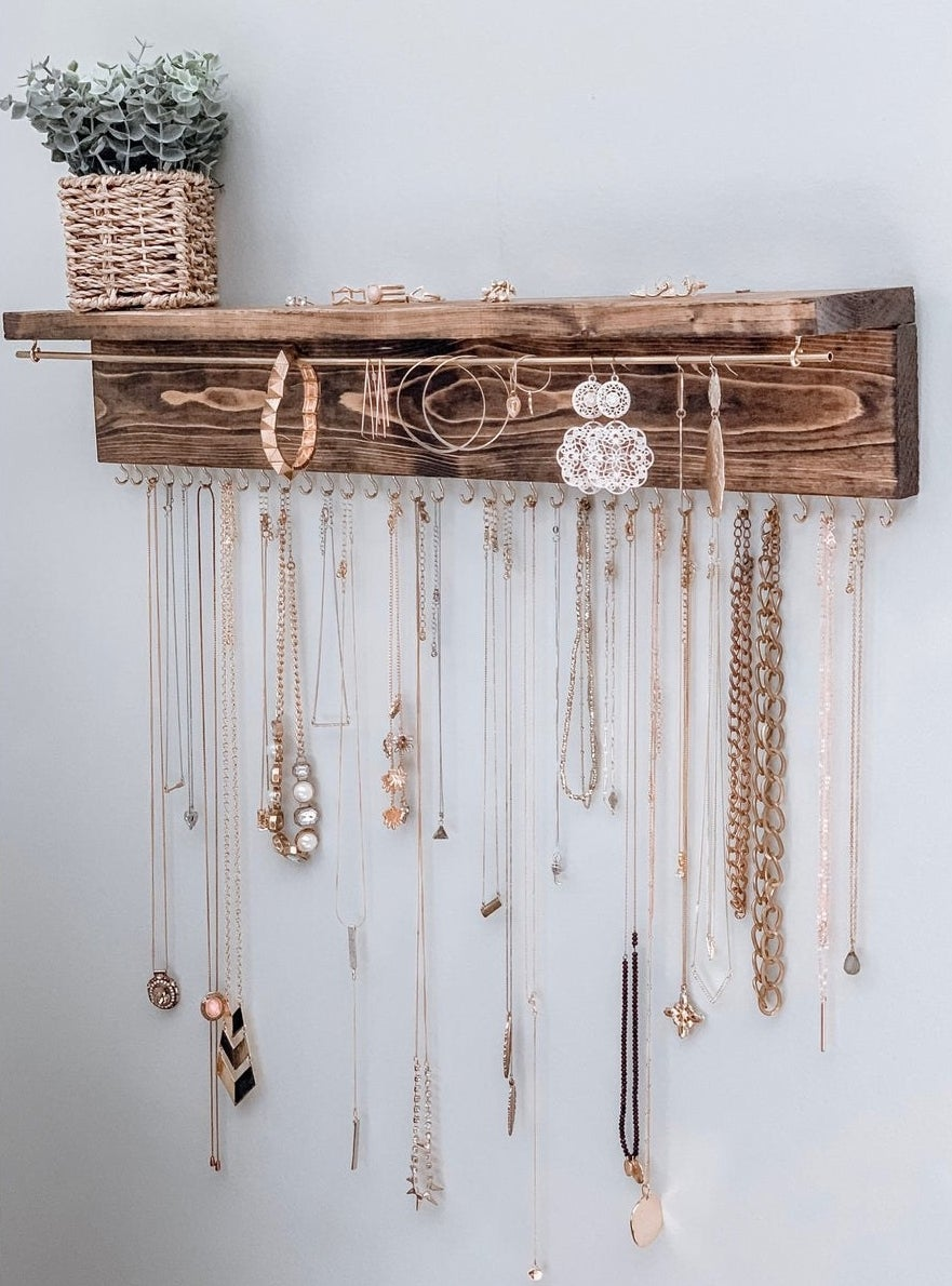 different necklaces, earrings, and bracelets hanging on the wooden wall-mounted organizer