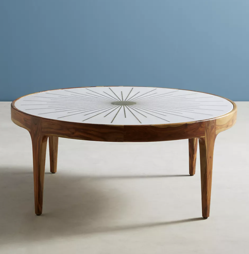 a brown rounded coffee table with a white table top and a gold starburst in the middle