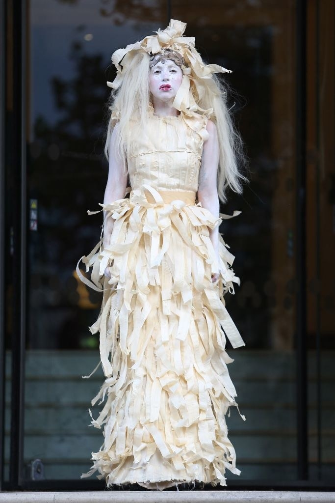 Gaga wearing a dress that looks like it's made of scraps of fabric along with white face and arm paint