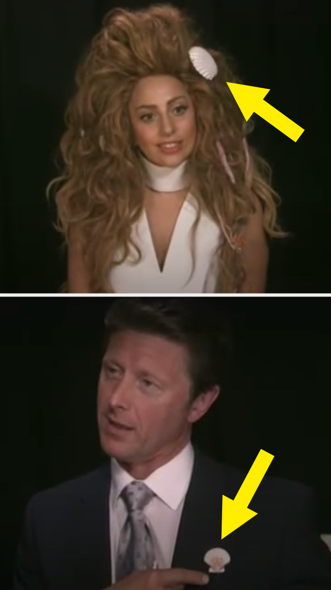 Gaga with a big wavy wig on that has a big seashell in it, and a reporter wearing a seashell pin