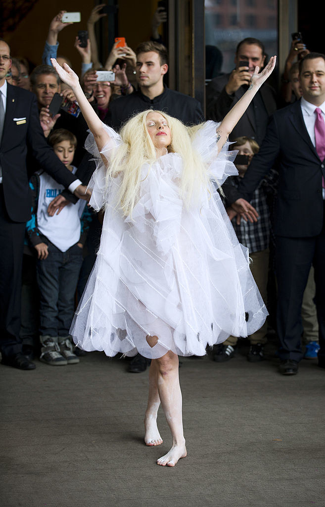 Gaga wearing a knee-length lace dress while doing a V with her arms