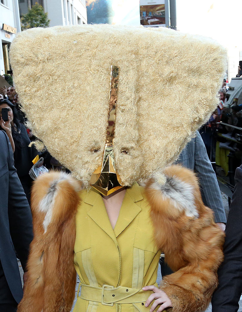 Gaga in a giant triangular headpiece that looks like it's made of fur