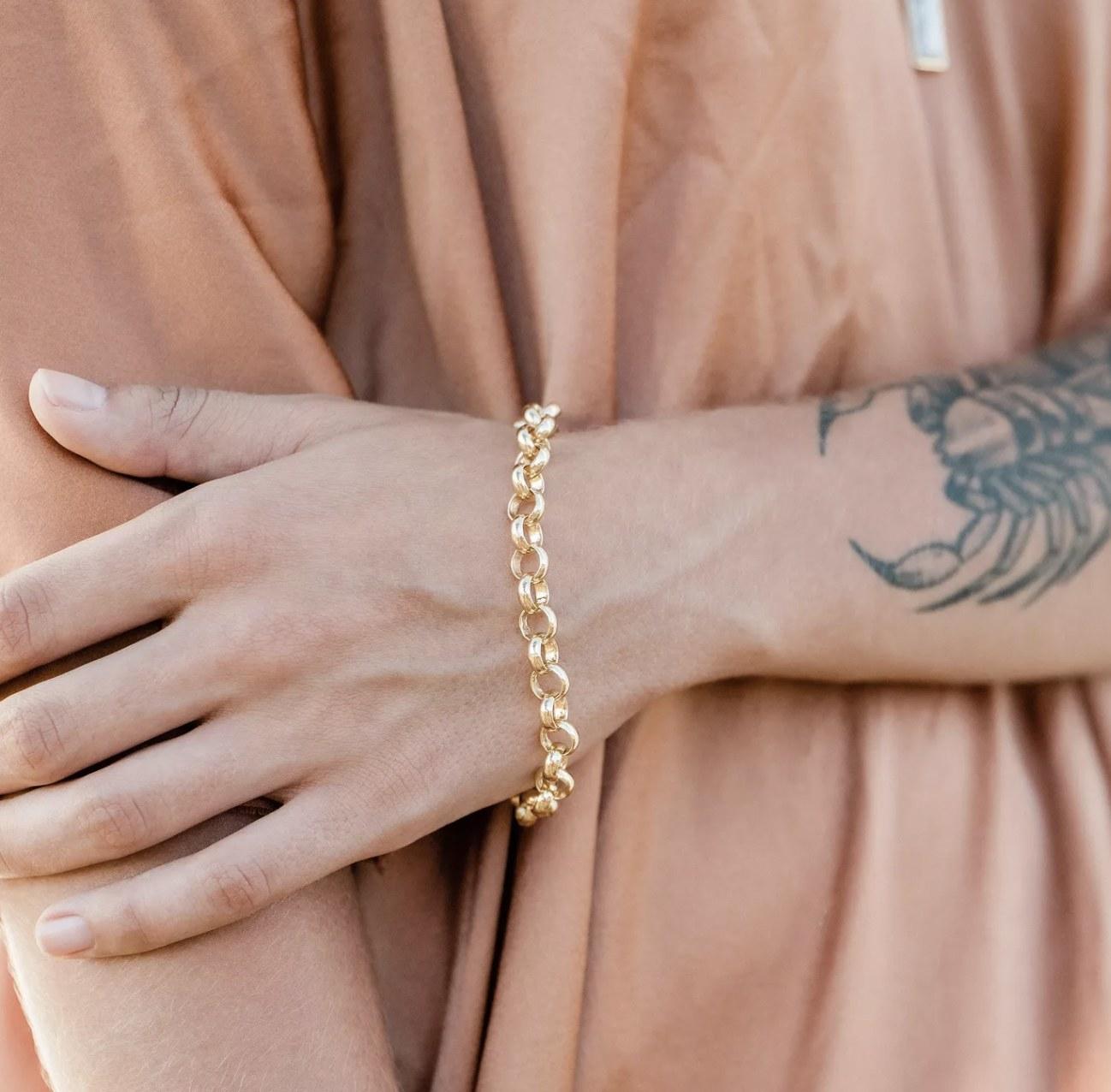 a gold round chain link bracelet on a model