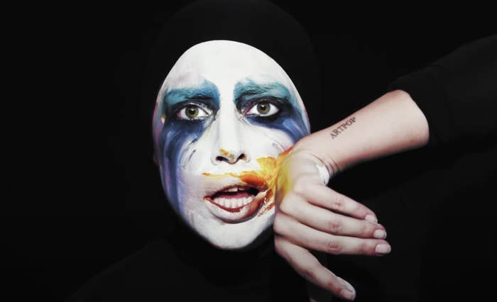 Lady Gaga in white face makeup and colors running down her face as she wipes her mouth and shows off the Artpop tattoo on her forearm