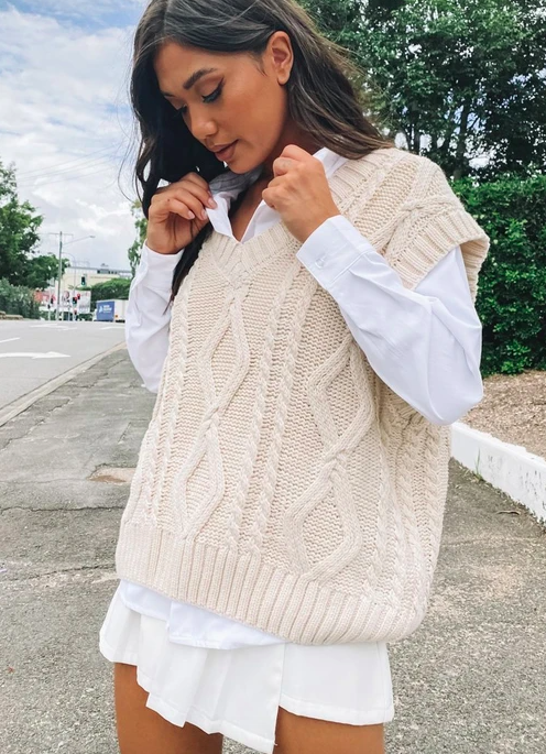 A model wearing the cable knit vest