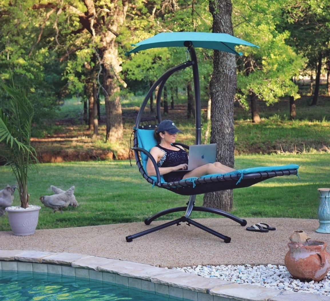 Reviewer sitting on the curved blue chair next to a pool