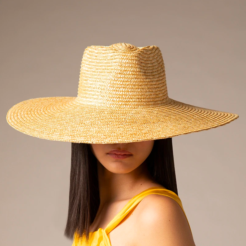 A person wearing the wide-brim hat