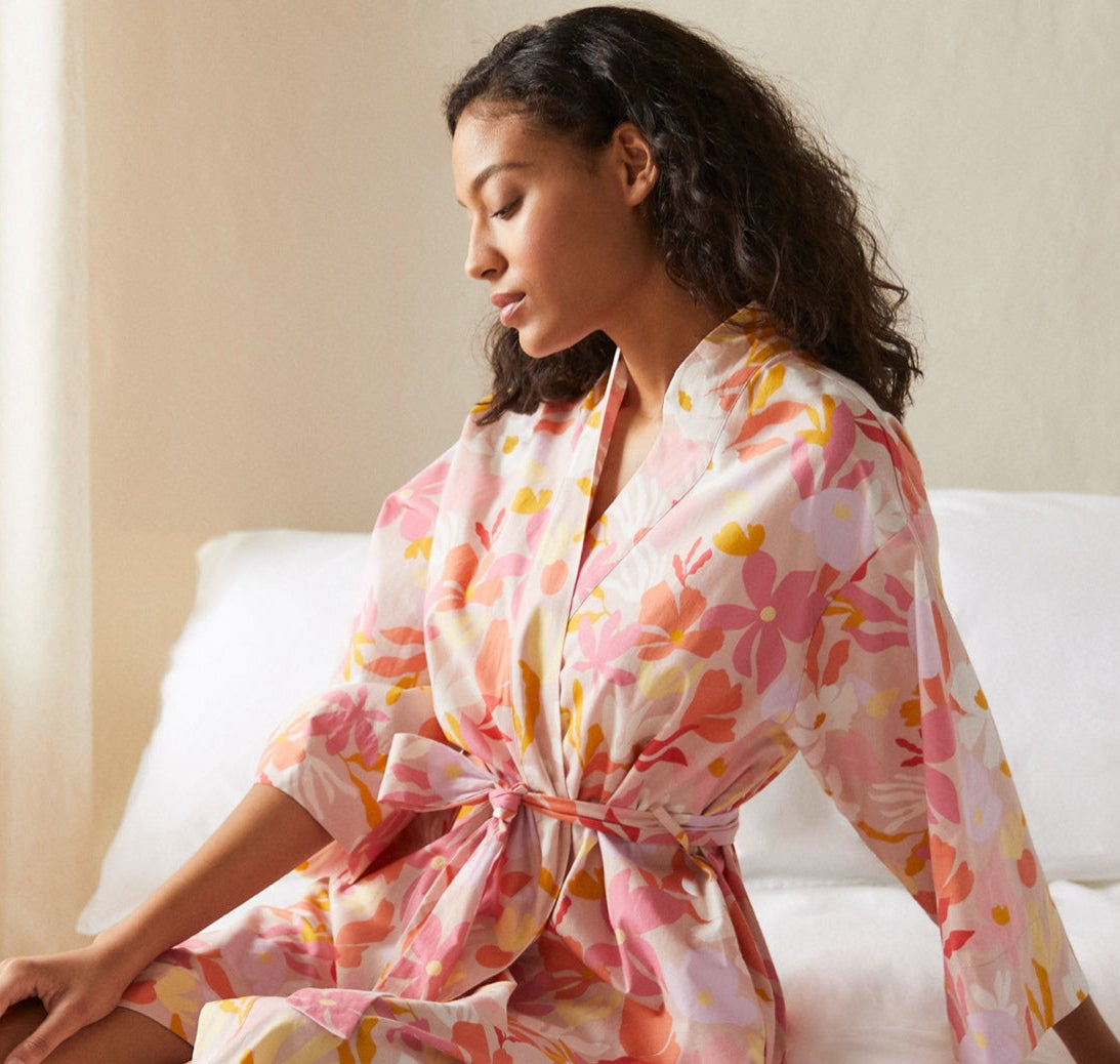 A person sitting on their bed while wearing the robe