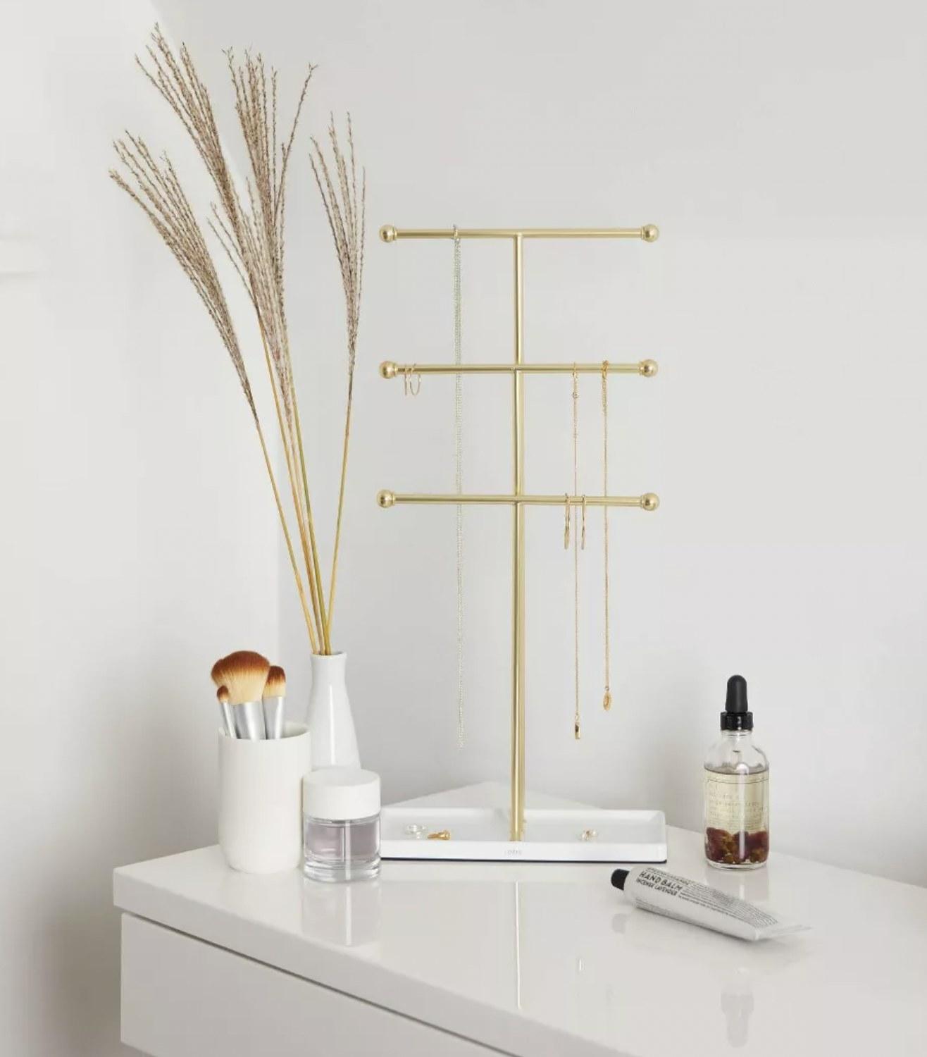 a brass jewelry stand holding necklaces, resting on a dresser