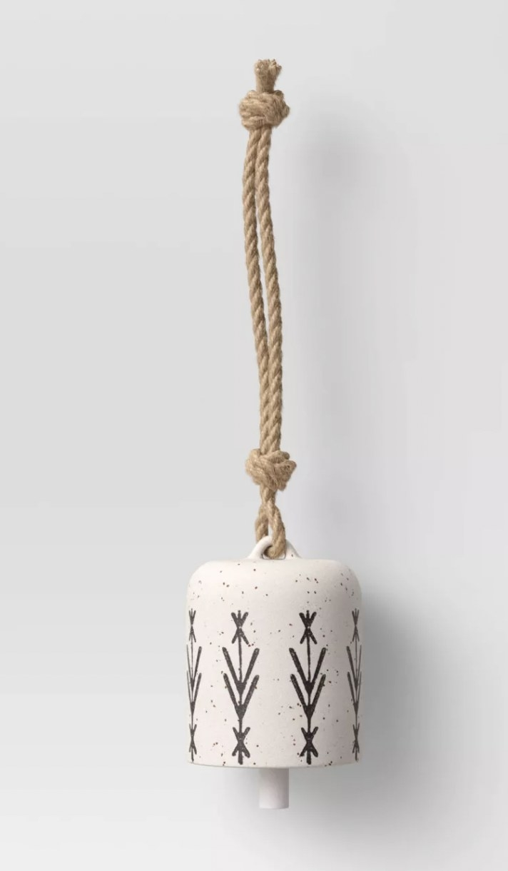 a white ceramic wind chime attached to a rope for hanging