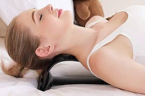 A model with her neck on the Magic Back Stretcher Lumbar Support Device