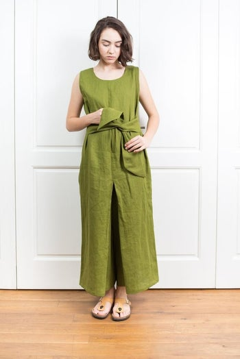 front view of a model tying a green jumpsuit
