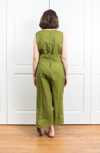 back view of the same model showing the jumpsuit has three buttons
