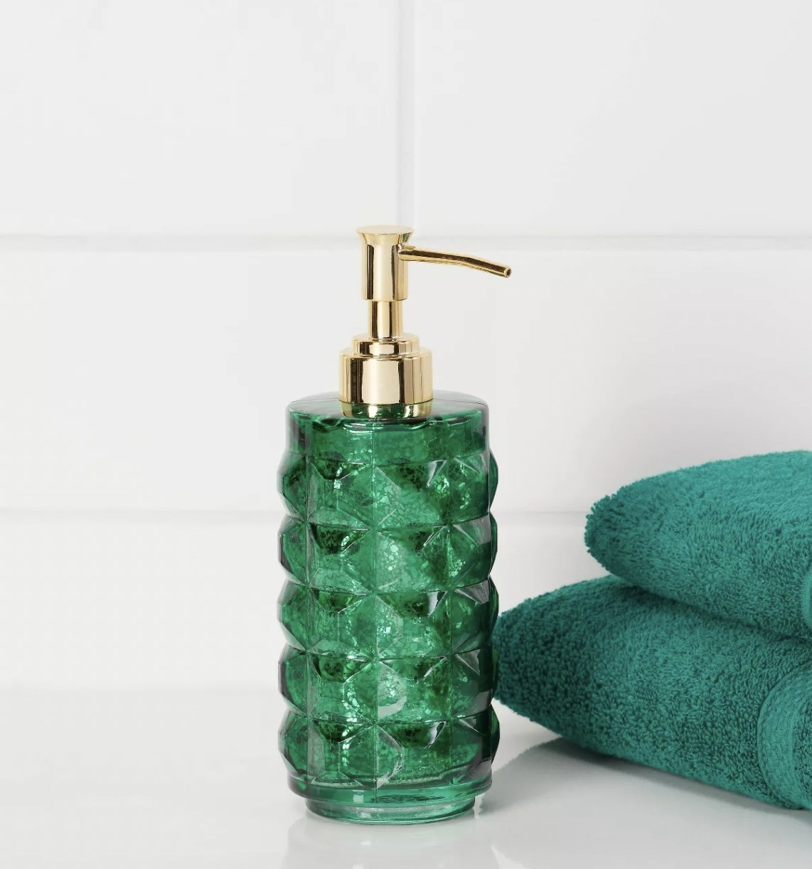 a green glass soap dispenser with a gold pump on a bathroom counter