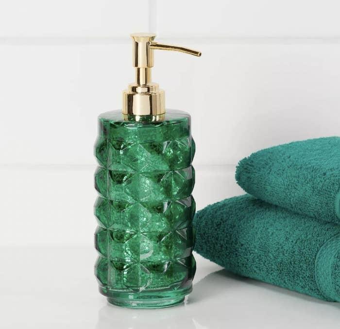 a green glass soap dispenser with a gold pump