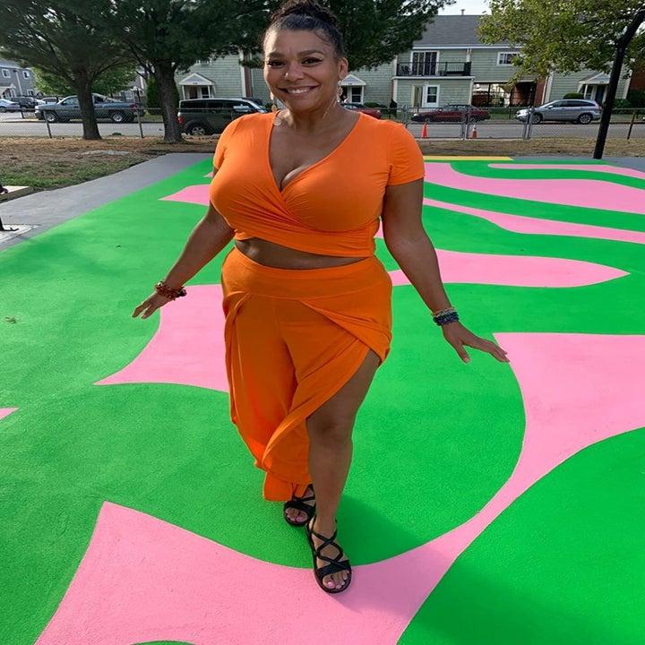 image of reviewer wearing the orange Vetior cross wrap crop top with matching orange skirt