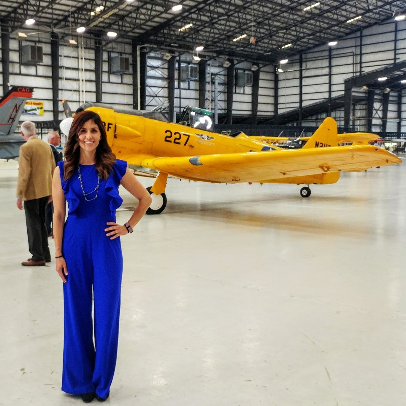 reviewer wearing the blue Romwe sleeveless ruffle trim jumpsuit at an airshow