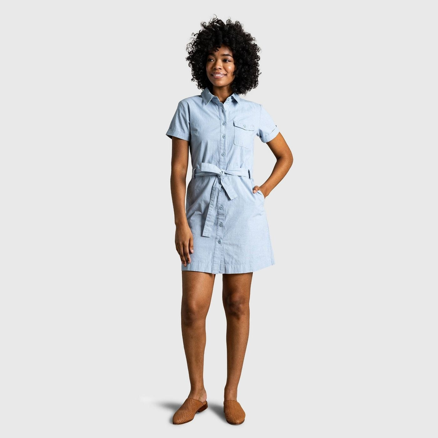 Model wearing blue dress with tie waist, goes past the thighs