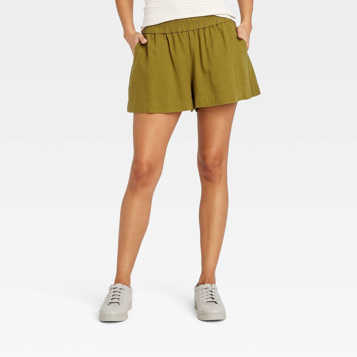 Model wearing green shorts that stop mid thigh