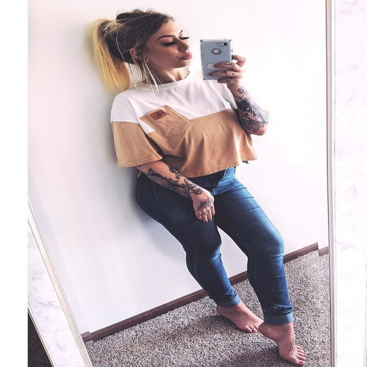 a reviewer wearing the top in apricot and white