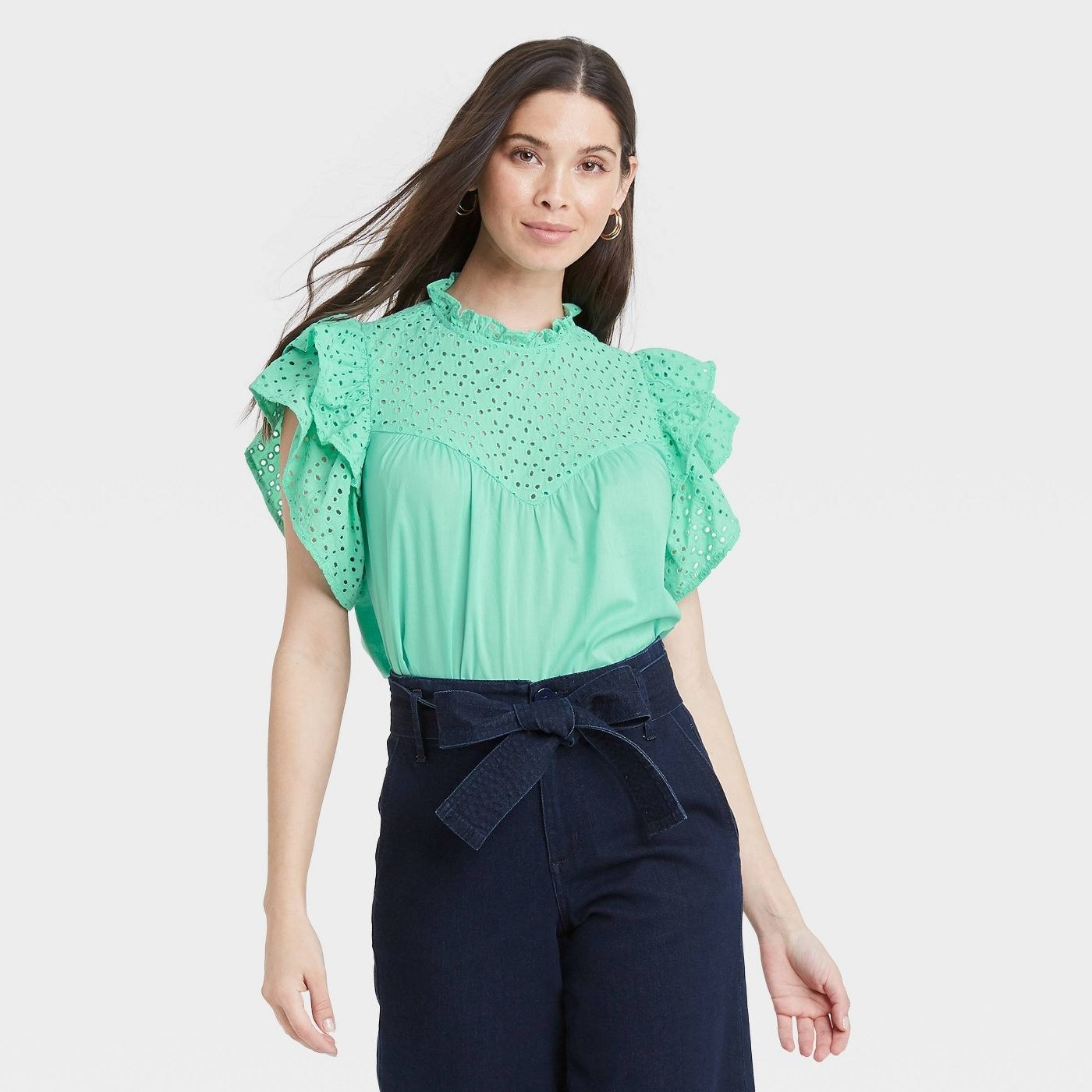 Model wearing sea green top