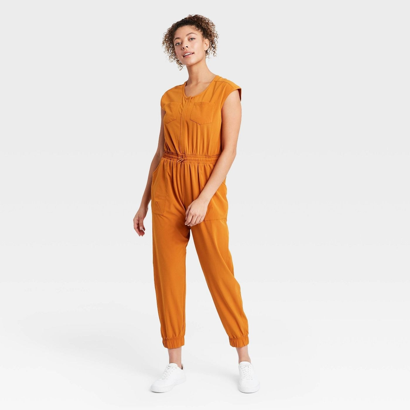 Model wearing mustard yellow jumpsuit cuffed at the ankle