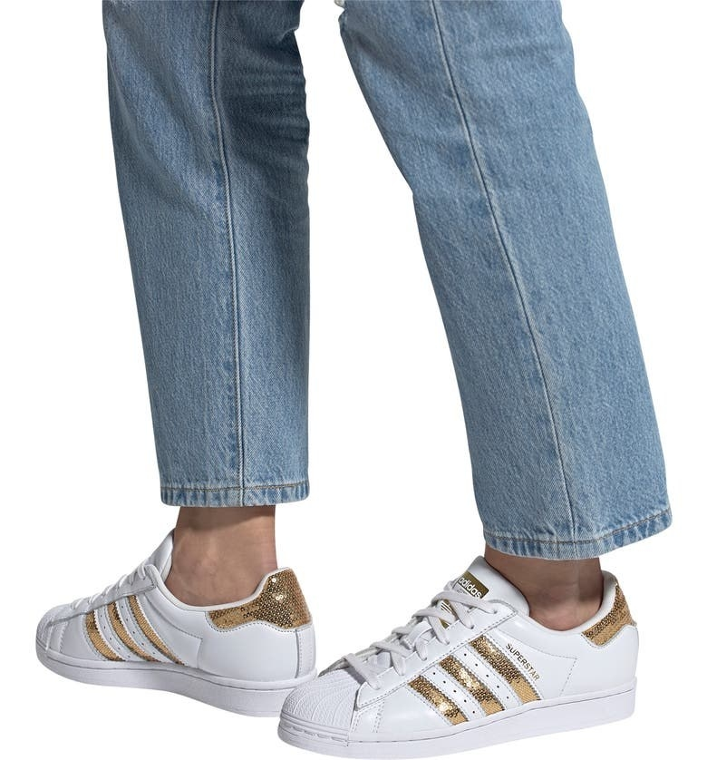 A model wears the shoes in gold