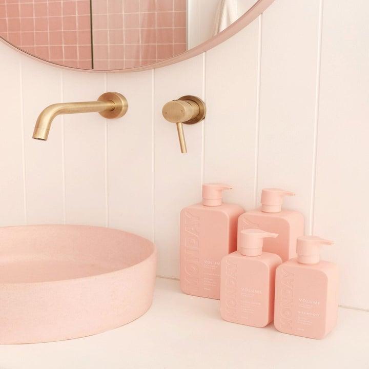 a bunch of blush pink pump bottles of shampoo